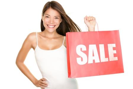 Mujer de venta comercial mostrando su bolsa de compras venta escrito. Hermosa mujer asiática sonriente mostrando bolsas de rojos. Mixto chino asiático caucásica modelo femenino aislada sobre fondo blanco. Foto de archivo - 9407145