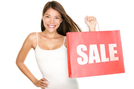 Shopping sale woman showing shopping bag with sale written. Beautiful smiling asian woman showing red shopping bags. Mixed Chinese Asian Caucasian female model isolated on white background. photo