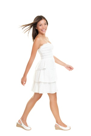 walking: Woman in white dress walking isolated on white in full length.  Beautiful fresh smiling young mixed race Asian Caucasian female model in cute summer dress.