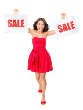 Sale - Woman showing shopping bags with sale written on them. Excited and cheering mixed race Chinese Asian Caucasian female model in red summer dress isolated on white background in full length. photo