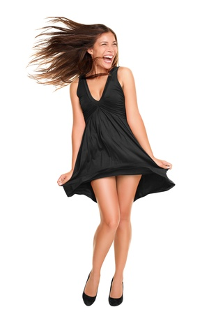 Playful funny woman excited standing in black dress. Beautiful happy mixed race Asian Caucasian model isolated on white background in full body. photo