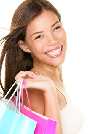 Shopping woman smiling holding shopping bags. Closeup portrait of beautiful young mixed race Asian Caucasian woman with gorgeous smile isolated on white background. Banco de Imagens