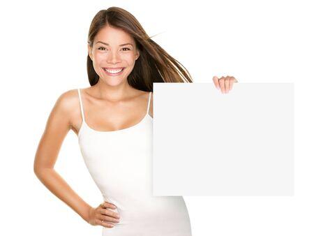 letreros: Mujer de signo de papel sonriendo. Linda chica dulce encantadora publicidad de su producto a bordo de signo blanco en blanco. Asia cauc�sica modelo femenino aislada sobre fondo blanco.
