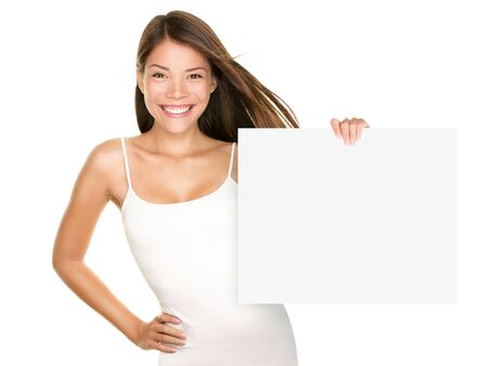 Paper sign woman smiling. Cute lovely fresh girl advertising your product on blank white sign board. Asian Caucasian female model isolated on white background. photo