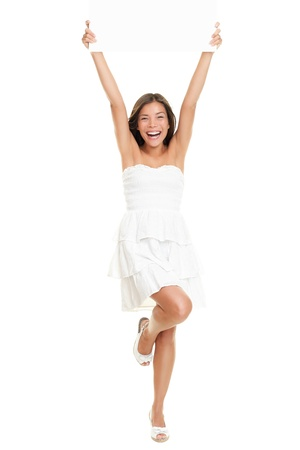 Dress woman holding paper sign in full body isolated on white background. Cute fresh cheering Caucasian Asian girl holding blank empty paper sign wearing a cute white summer dress. 스톡 콘텐츠