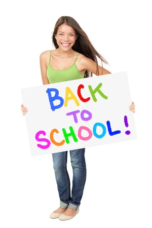 University student holding back to school sign standing isolated on white background. Asian Caucasian female student smiling happy. Foto de archivo