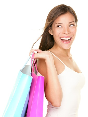 looking over shoulder: shopping woman happy looking at empty copy space. Isolated on white background. Beautiful Asian Caucasian female shopper. Stock Photo