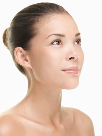 tratamiento facial: Cerca de cuidado de piel de mujer de belleza asi�tica. Hermosa joven tocar su cara mirando al lado. Aislados sobre fondo blanco. Modelo asi�tico  cauc�sica de raza mixta.