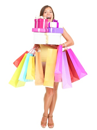 happy shopper: Shopper. Shopaholic shopping woman holding many shopping bags excited. Isolated portrait of young woman in full body on white background. Stock Photo