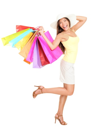 gift bags: Asian shopping woman happy smiling holding many shopping bags. Asian shopper girl isolated on white background in full length wearing summer hat. Stock Photo
