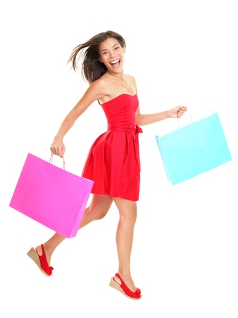Shopper - woman shopping holding shopping bags in red summer dress. Young asian woman walking cheerful and smiling isolated in full body on white background. Mixed race Asian  Caucasian female model. Banco de Imagens