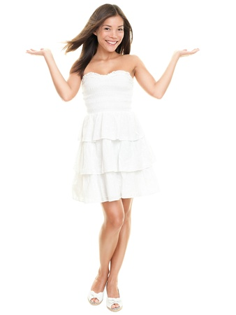 shrugging: Woman showing with two open hands. Beautiful lovely girl in white summer dress isolated on white background in full body. Stock Photo