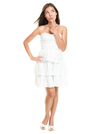 Beautiful woman thinking happy looking up wearing white summer dress.. Sexy gorgeous multiracial Asian / Caucasian female model isolated on white background in full figure.