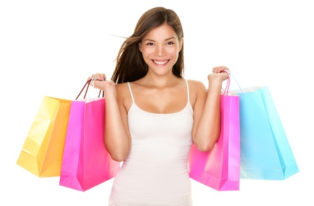 Shopping woman happy smiling holding shopping bags isolated on white background. Lovely fresh young mixed race Asian Caucasian female model. Stock Photo