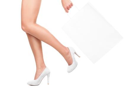 piernas con tacones: Compras. Con bolsa de compras con espacio de copia de texto. Detalle de las piernas de la mujer aisladas sobre fondo blanco.