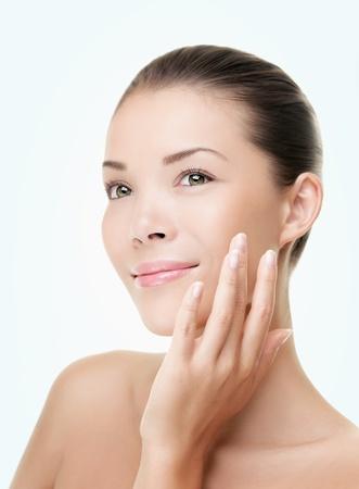 cute: Donna di pelle cura bellezza. Bellezza donna sorridente applicando crema. Ritratto di bellezza di bella modello femminile Asian  indoeuropeo isolato su sfondo azzurro guardando copy space. Archivio Fotografico