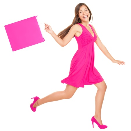Happy shopping woman in pink running with shopping bags. Isolated on white background in full length. photo