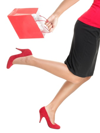 Shopping woman holding red shopping bag running. Photo is isolated on white background. photo