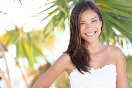 Vacation woman smiling on tropical beach summer holidays with palm trees. Portrait of pretty happy mixed race Caucasian  Asian female model. photo