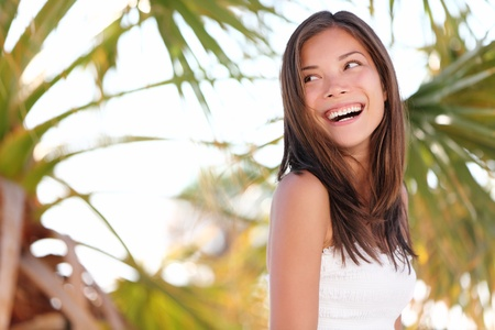 Beach holidays woman smiling looking over her shoulder on tropical beach summer vacation with palm trees. Portrait of beautiful happy mixed race Caucasian  Asian female model in summer dress photo