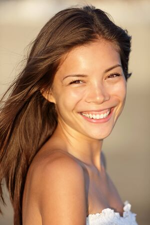 mosolyogva: Beach woman smiling happy portrait. Beautiful young mixed race Asian  Caucasian woman portrait. Natural smile on beach at sunset.