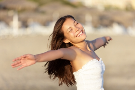 Carefree beach woman happy and serene smiling on beach at sunset. Joyful beautiful young mixed race Asian / Caucasian woman portrait.