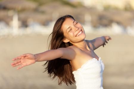 Zorgeloos strand vrouw gelukkig en serene glimlach op strand bij zonsondergang. Vrolijke mooie jonge gemengd ras Aziatische  Kaukasische vrouw portret.