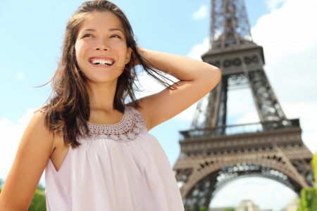 Paris woman tourist at Eiffel Tower smiling happy. Beautiful Caucasian Asian girl enjoying her Paris travel. Standard-Bild