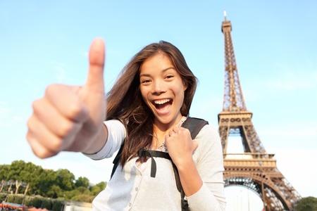 パリ エッフェル塔観光幸せなバックパックを背負ってヨーロッパで。陽気な笑みを浮かべて女性観光、エッフェル塔の前で成功登録して親指を示す
