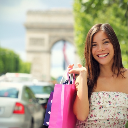 elysees: Paris shopping woman tourist on Champs-with Arc de Triomphe in the background carrying shopping bags outside in Paris. Pretty Asian Caucasian female model. Stock Photo