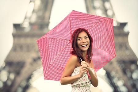 lloviendo: Paris Eiffel Tower mujer feliz sonriendo de atracción turística Torre Eiffel. Alegre fresca Cáucaso asiático chica riendo. Foto de archivo