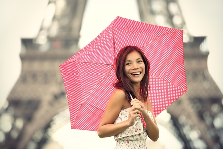 is raining: Paris Eiffel Tower Woman happy smiling in front of tourist attraction Eiffel Tower. Joyful fresh Caucasian Asian girl laughing. Stock Photo