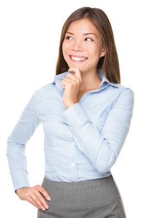 donna pensiero: Pensando donna d'affari asiatica sorride guardando al lato. Giovane e bella razza mista asiatica caucasica donna professionale isolato su sfondo bianco.