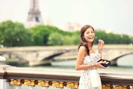 invalides: Paris woman smiling eating the french pastry macaron in Paris. Eiffel tower and Pont Des Invalides in the background. Cute beautiful mixed race Asian Caucasian female model.