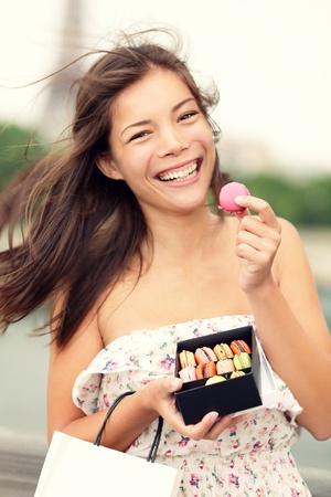 マカロン: パリの女性が幸せと笑顔のパリでマカロンを食べてします。エッフェル塔をバック グラウンドで。かわいい美しい混合レース アジア白人女性モデル ドレス サマードレス小さなショッピング バッグを保持で遊び心のあります。