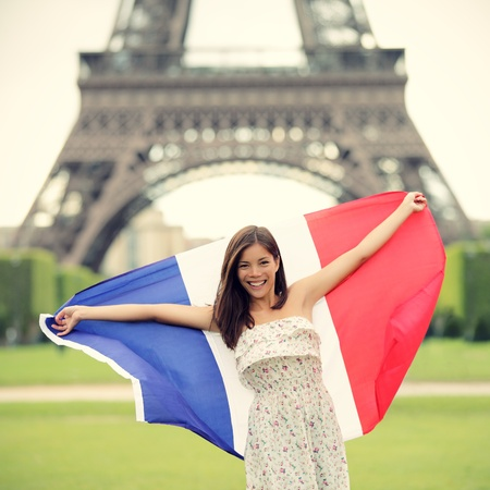 student travel: Paris woman holding French flag by the Eiffel Tower in Paris. Tourist on travel in europe. Stock Photo