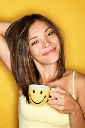 breakfast smiley face: Morning Coffee Woman Tired drinking coffee smiling happy and candid. Cute mixed-race Asian Caucasian female model on yellow background. Stock Photo