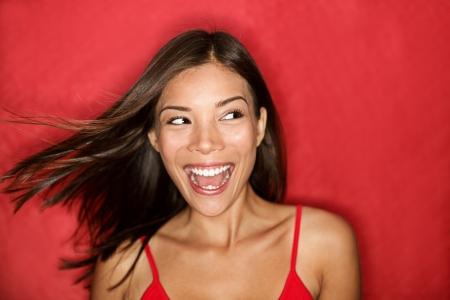 cara sorprendida: Feliz emocionada mujer mirando para el lado gritando jovial con el viento en el cabello sobre fondo rojo. Hermosa multirracial asiáticos caucásica modelo femenino.