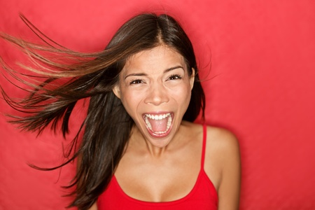 Scream. Woman screaming wild and crazy at full energy looking at camera on red background. Beautiful mixed race Asian Caucasian brunette female model with wind in the hair. 免版税图像