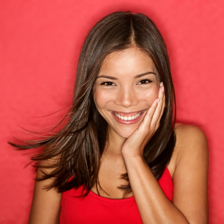face to face: Smiling young woman - cute portrait. Natural candid adorable smile on Asian Caucasian girl on red background. Stock Photo