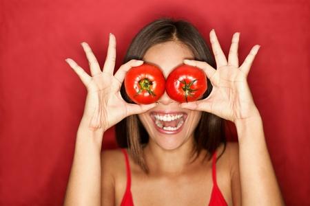 frutas divertidas: Tomate. Mujer mostrando tomates los retienen en delante de los ojos. Nueva imagen divertida en�rgica sobre fondo rojo.