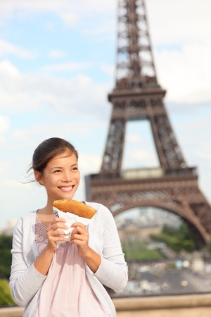 Paris woman and Eiffel Tower. Girl eating french crepe  pancake in front of Eiffel Tower, Paris, France. Mixed race Chinese Asian  Caucasian tourist.