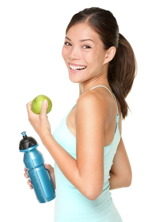 Fitness woman happy smiling holding apple and water bottle. Healthy lifestyle photo of Asian Caucasian fitness model isolated on white background. Stock Photo