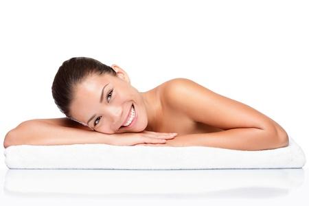 美女: 水療中心。臉護膚美容女人微笑快樂。美麗誘人的混血中國亞洲白人女性模型,皮膚護理治療期間躺在毛巾上的肖像。女孩被隔絕在白色背景。 版權商用圖片