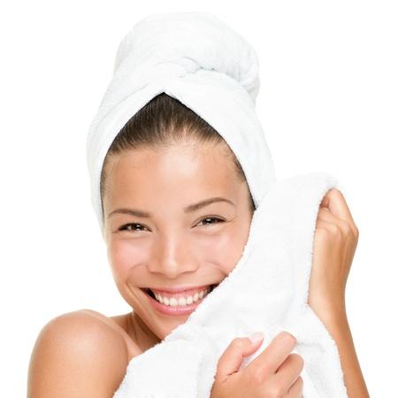 toalla: Mujer de spa belleza tratamiento sonriente toalla suave sensaci�n feliz en la cara. Detalle de la hermosa Linda raza mixta China Asia  cauc�sica modelo femenino con piel perfecta. Chica aislada sobre fondo blanco