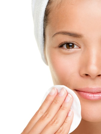 piel: mujer de cuidado de piel quitar maquillaje de cara con almohadilla con un hisopo de algod�n - concepto de cuidado de piel. Detalle facial de bastante hermosa raza mixta China Asia  cauc�sica modelo femenino con piel perfecta. Chica aislada sobre fondo blanco