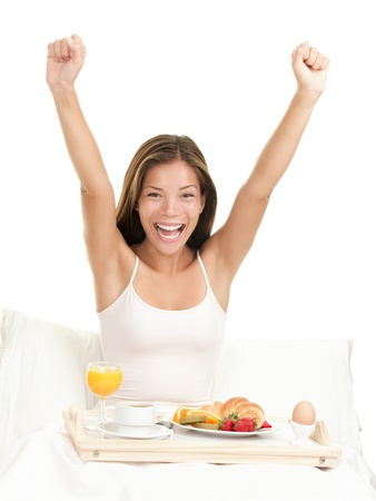 Happy morning breakfast woman smiling eating breakfast in bed stretching looking at camera.