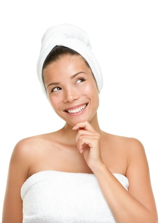 woman in bath: Happy spa woman thinking looking up isolated on white background. Beautiful smiling Asian Caucasian with towels. Stock Photo