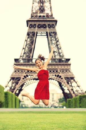 幸せな笑顔をジャンプでエッフェル塔パリ女の子赤い夏のドレスで興奮しました。うれしそうな若い女性の休暇中に陽気なシャンゼリゼパリ、フラ