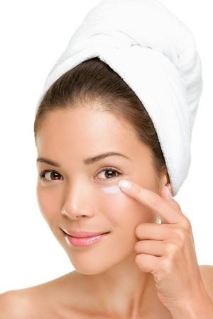 limpieza de cutis: Mujer de atenci�n poniendo crema tocar bajo los ojos de la piel. Detalle de la belleza facial de bella mestiza Asia  cauc�sica modelo aislada sobre fondo blanco.
